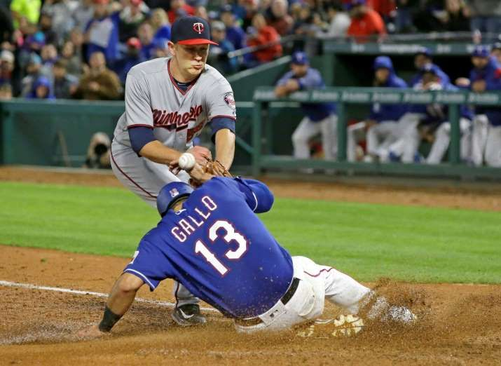 TOO HARD TO HANDLE:    Minnesota Twins relief pitcher Tyler Duffey, top, can't handle the ball, allowing Texas Rangers Joey Gallo to score on a wild pitch during the sixth inning on April 26 in Arlington, Texas. The Rangers won 14-3.