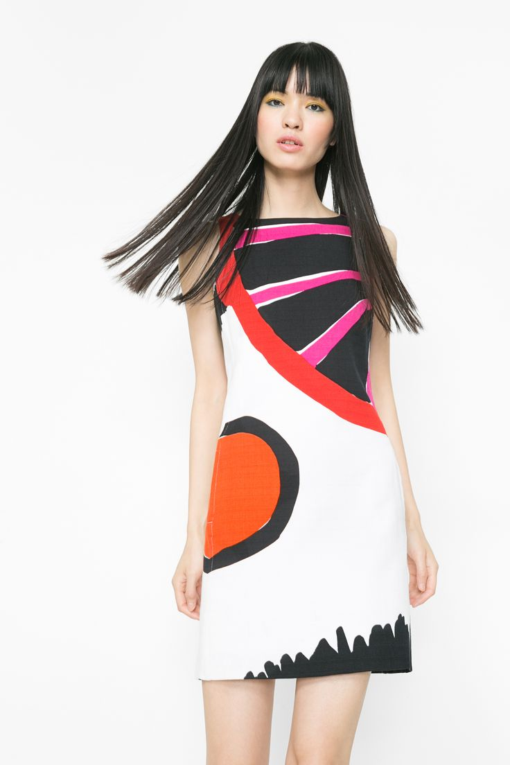 A short, sleeveless pinafore dress that's soft and has a print that combines white and bright colors. It's designed by Mr. C. Lacroix and has a playful zipper.