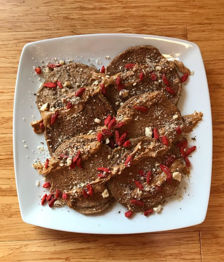 homemade banana oat pancakes topped with peanut butter goji berries and hazelnut crumbles