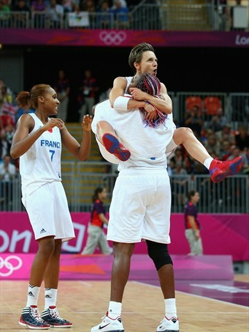 France captain Celine Dumerc celebrates with team mate Isabelle Yacoubou after winning the women's Basketball Preliminary Round match between Australia and France on day 3.