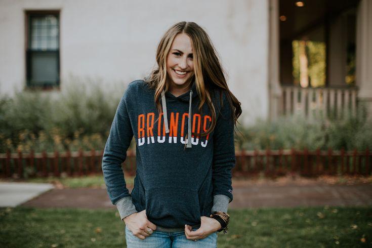 Womens NFL Broncos Hoodie girl wearing navy Denver Broncos Hoodie with brown curled hair and skinny distressed denim
