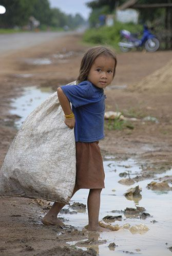 A young girl in Kampong Cham, Cambodia, collecting used plastic bottles to sell for a few pence.