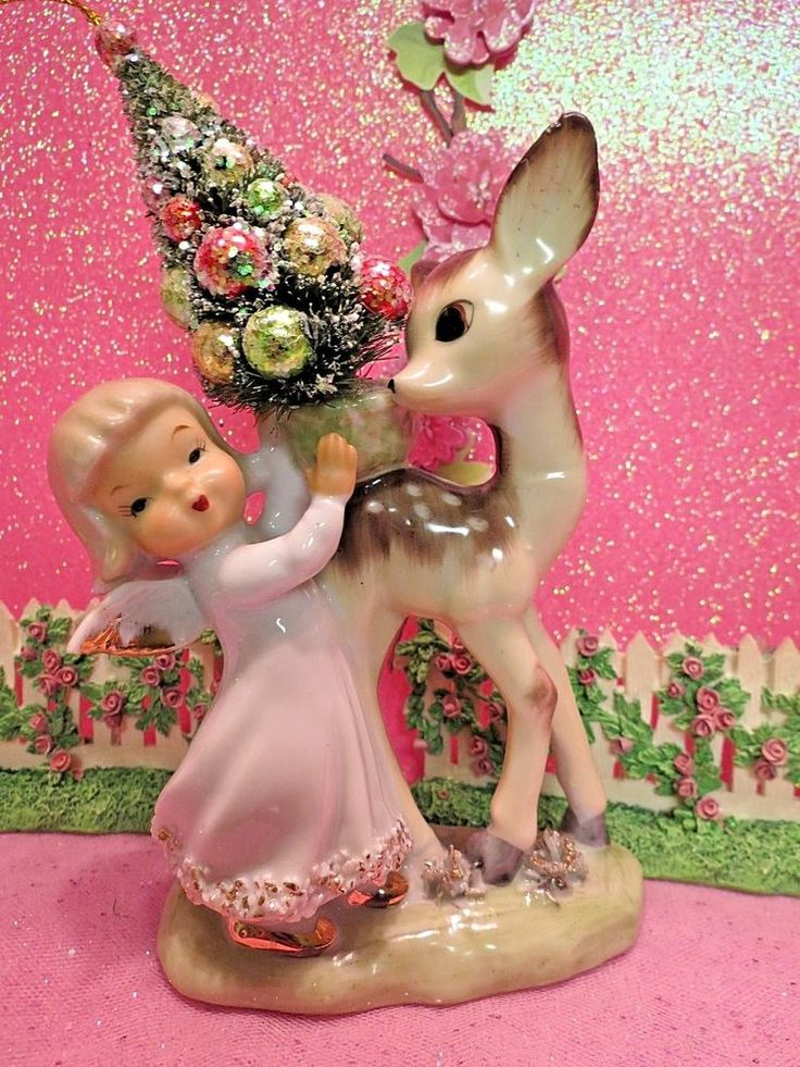 "The little angel has blonde hair and the cutest little gold trimmed wings. They are standing on a woodland grassy knoll with ""spaghetti"" grass and the little angel is wearing tiny gold shoes. The fawn deer is looking over his back to see what she is doing. 