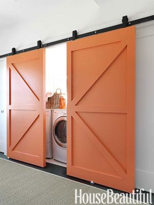 "A Laundry Room With a Twist  Barn doors painted the same bold orange pack a punch in the laundry area. ""The doors to the laundry room could have been a lost opportunity—just another pair of white doors,"" says Berman. ""But we felt they shouldn't be an afterthought. Painting them orange made them very visible and special. They read as art."""