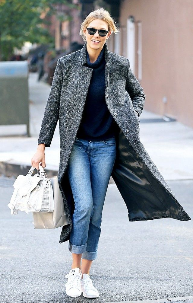 Karlie Kloss wears a gray trench coat with a navy blue turtleneck, cuffed jeans, a Proenza Schouler PS1 shoulder bag, and Adidas Originals Stan Smith sneakers