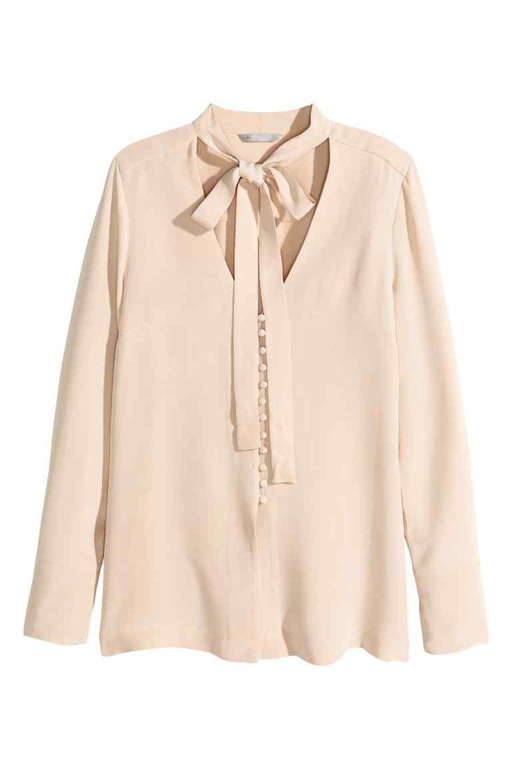 Blusa de seda: QUALIDADE PREMIUM. Blusa de seda natural com laçada no decote em V. Tem botões forrados na frente e nos punhos e racha alta nos lados.