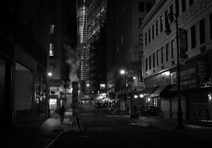 New York City at night - Financial District street with a smoke stack.  At night after the multitudes have retreated to their homes away from the buildings and streets that hold them close during the day the city relaxes shaking the dust of the long day from its concrete limbs.  The street lights flicker like dream-heavy blinks of an eye while smokestacks exhale world-weary breaths of smoke into the yawning night air.   —-  View this photo larger and on black on my Google Plus ...
