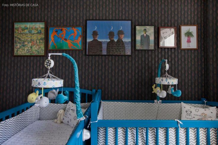 Quarto de bebê com papel de parede preto, coleção de quadros  e berços azuis.