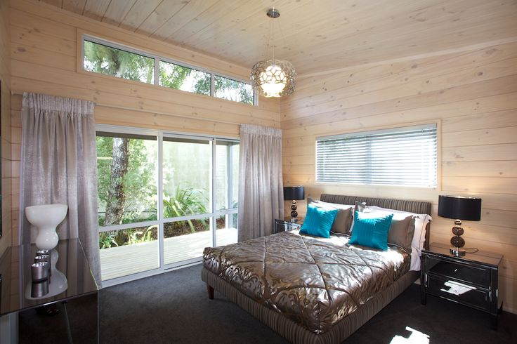 High clerestory windows, with modern charcoal mirror furniture, blonded interior Lockwood walls of this main bedroom