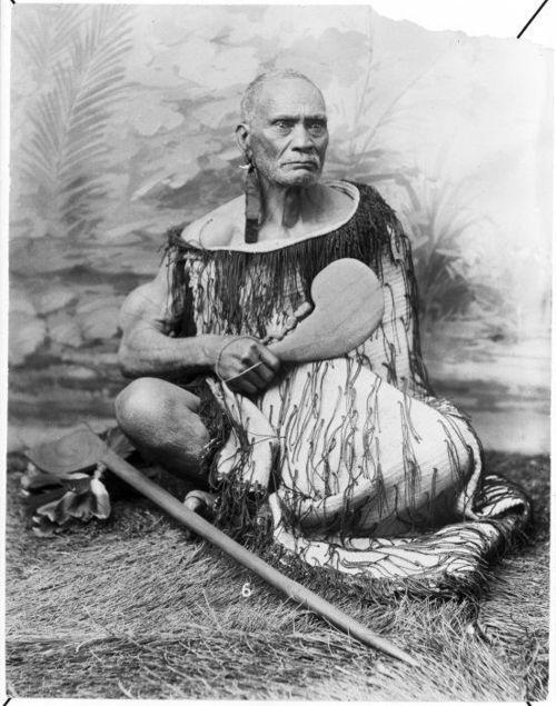 Take Take Rangitupu from Ranana, Wanganui River, ca 1880s  Seated  studio portrait of Take Take Rangitupu from Ranana, Wanganui River. He  wears an ear adornments made of ribbon and an animal tooth. He wears a  korowai (Maori tag cloak) and holds a patu. A tewhatewha lies at his  feet. He sits before a painted backdrop. Photograph taken circa 1880s.  Photographer unidentified.