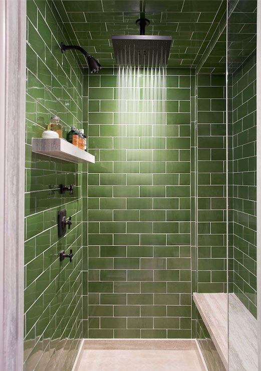 Walk-in shower boasts green subway tiled surround and ceiling accented with ceiling mounted square rain shower head over secondary shower head and marble floating shelf across from marble top shower bench.