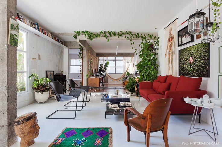 Sala de estar tem estrutura de concreto aparente, sofá vermelho e poltronas Paulistano.