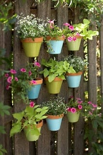 Painted pots on a gray fence.