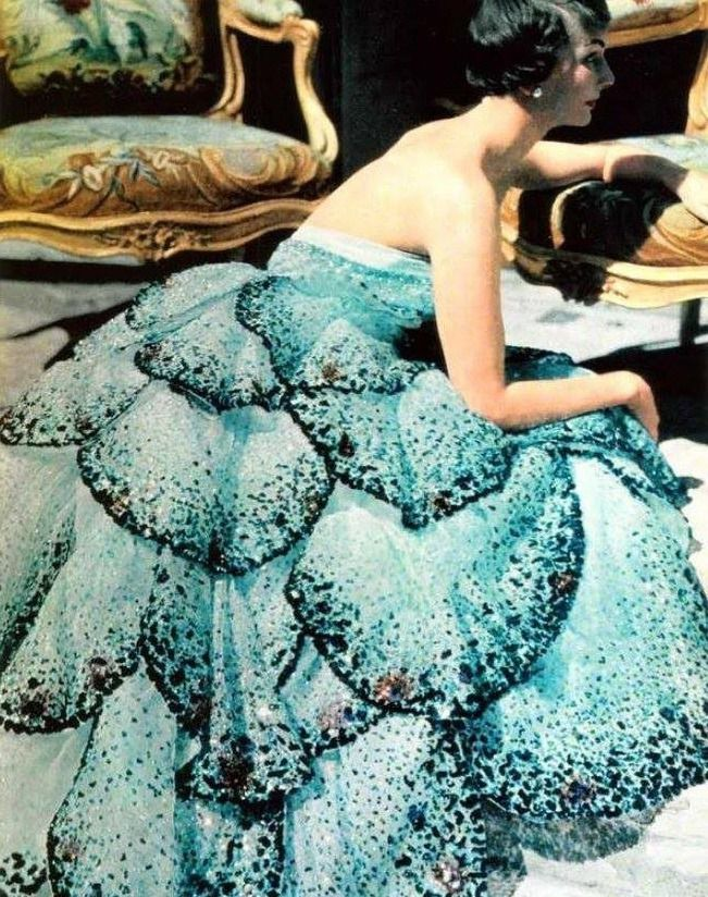 В 1947 году Кристиан Диор создает свою коллекцию от кутюр. Она была блистательной и скандальной. Обедневшая Европа погрязла в эпохе «сделай сам», все платья, сумки и даже шляпки 40-х годов были созданы в режиме жесткой экономии, а тут прекрасная, шикарная по-парижски коллекция, платья с пышными юбками-колокольчиками, кстати, коллекция так и называлась — «Колокольчик». Это главный редактор