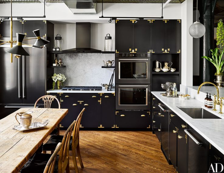 In the loft's kitchen, brass luggage corners outline the sleek black cabinetry.
