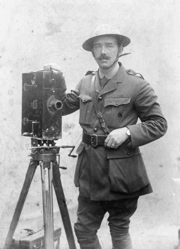 Portrait of J B McDowell, one of the British official cameraman on the Western Front during the First World War, photographed wearing a steel helmet and posed with a Moy and Bastie cine camera.