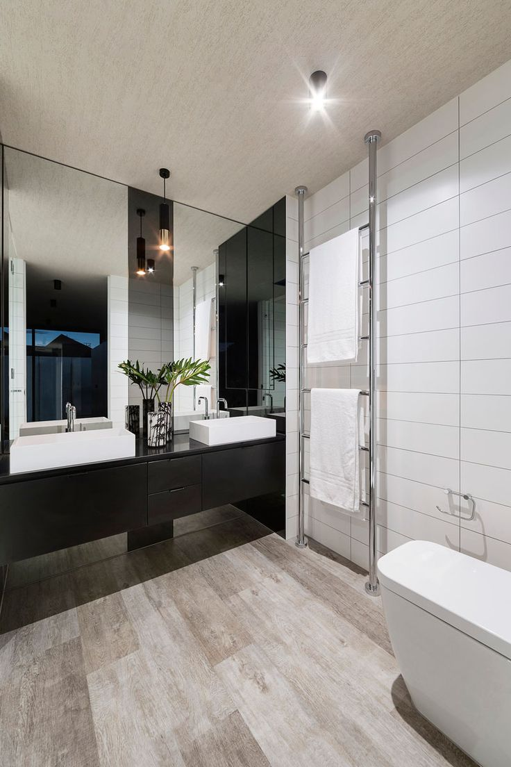 This bathroom has dual sinks, large white tiles, and a towel rack that goes from the floor to the ceiling.
