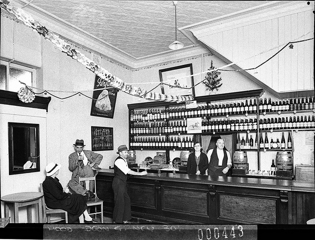 Penfold's Wines display in a wine bar; proprietor and his wife behind the bar and three customers, January 1939 by Sam Hood  Find more detailed information about this photograph collection: http://acms.sl.nsw.gov.au/item/itemDetailPaged.aspx?itemID=12188  From the collection of the State Library of New South Wales http://www.sl.nsw.gov.au