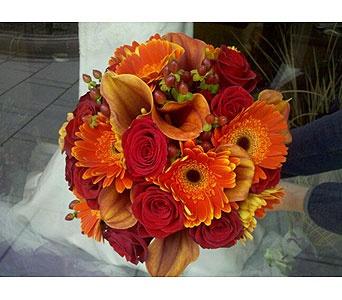 Hand tied bouquet of red roses, Mango mini callas, orange gerber daisies and brown hypericum berries .