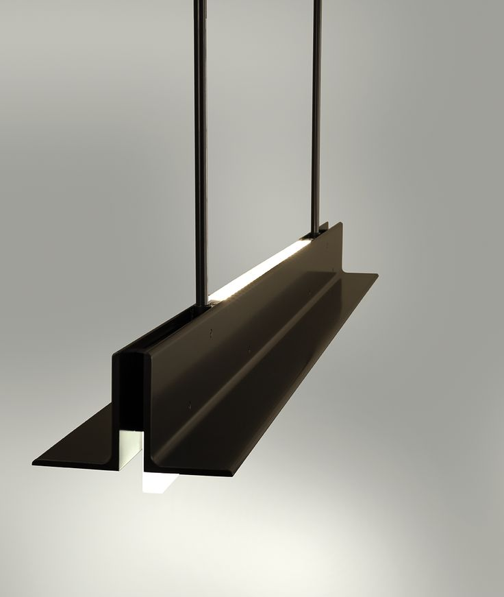 """Boyd Lighting's T-Light Pendant was designed by Joshua Aidlin of Aidlin Darling Design. The linear pendant features parallel pieces of extruded aluminum that hang from two stems and sandwich a ¾"""" thick piece of etched, water white glass, which form an upside down """"T"""". Two strips of LEDs provide warm up and down-light and are wired as dual circuits, which allows each light source to be dimmed separately. Comes in a 8 standard powder coat finish options, and is available in 5', 6' and 7'…"""