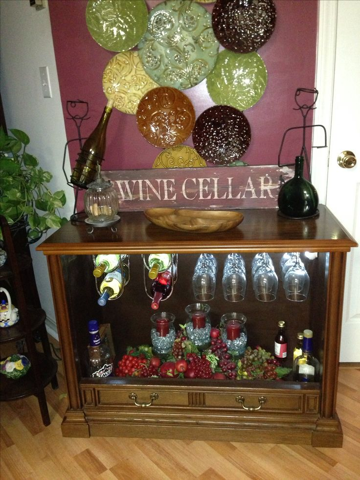 I took the insides out of an old console tv cabinet and put it on casters. I painted the inside dark brown and installed stainless steel wine racks and glass racks from Home Depot and turned it into a rolling wine bar.