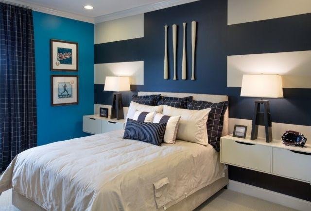 chambre enfant garçon avec un grand lit coussins et peinture murale bleue