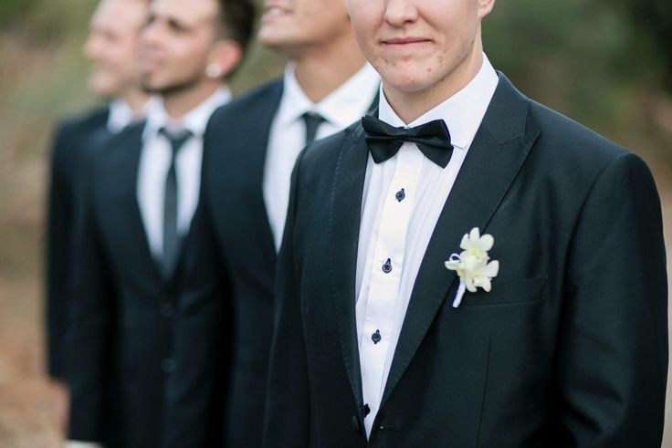 Beautiful groom with his suit and bowtie and groomsmen all dressed in black and white #blackandwhite #groom #suit #bowtie #wedding #inspiration