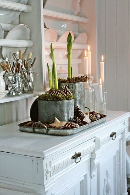 Open shelves with glass and cutlery on display, Amarylis flower bulbs in old containers, all on a tray, white candles in glass, everything together on top of a cabinet painted white - VIBEKE DESIGN