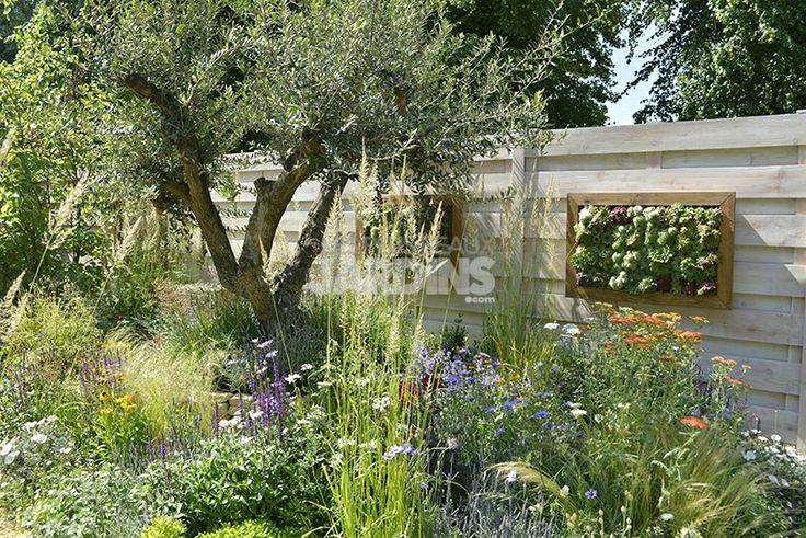 Un tableau accroch la palissade en bois brut un jardin - Accroche tableau 3m ...