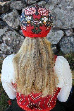Kvinna i dräkt från Delsbo socken, Hälsingland. Kvinnorna i Delsbo hade håret utsläppt under mössan, både som ogifta och gifta.