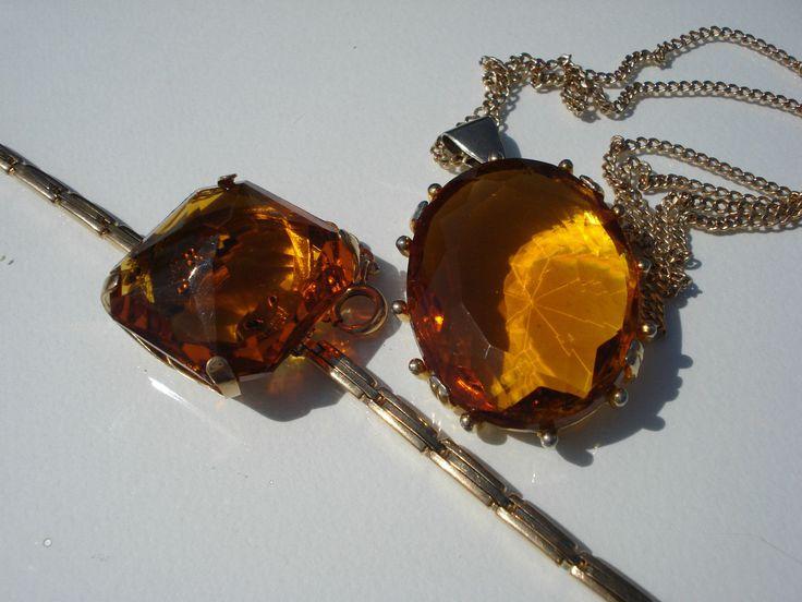 JOLI Lot De Deux Bijoux Anciens/pl Or/verre Orange/bracelet/pendentif - EUR 50,00. Joli lot de deux bijoux anciens avec éléments en verre de couleur jaune orangé le bracelet est composé d'un bracelet de montre ancien en plaqué or, légèrement extensible dans ses maillons, avec verre de forme carrée il mesure 17 cm à 20 cm une fois étiré, large griffe tenant la pierre qui mesure 2,8 x 2,8 cm le pendentif, des années 50/60 est en métal doré, il mesure 5,5 cm en longu...