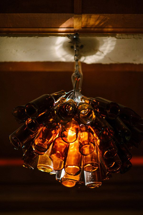 Who knew a beer bottle chandelier would be romantic? | Milton Photography | See More: http://heyweddinglady.com/ruby-and-gray-wedding-with-vintage-book-details-from-milton-photography/