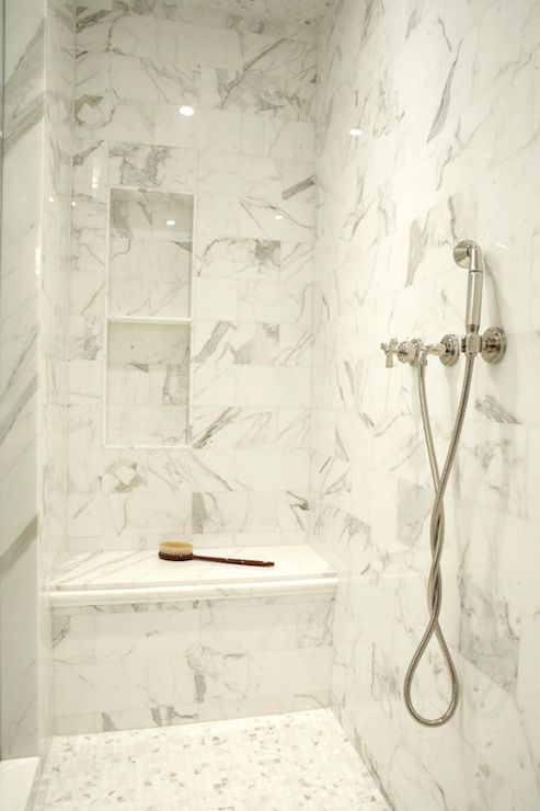 Fabulous walk-in shower with gray and white marble tiled walls and recessed tiled niche over a built-in shower bench with an adjustable shower head to the right over marble mosaic tiled floors.