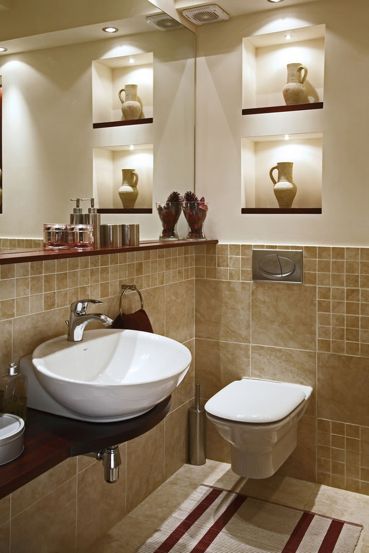 I love how the toilet and sink take up hardly any room. And then there is the in wall shelves and the long shelf under the huge mirror.
