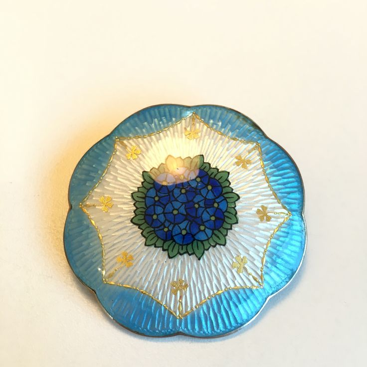 Gustav Gaudernack design for own workshop.Silver guilloché enamel brooch with enamel painting of stylized flowers and inlaid gold details. 1910-1914