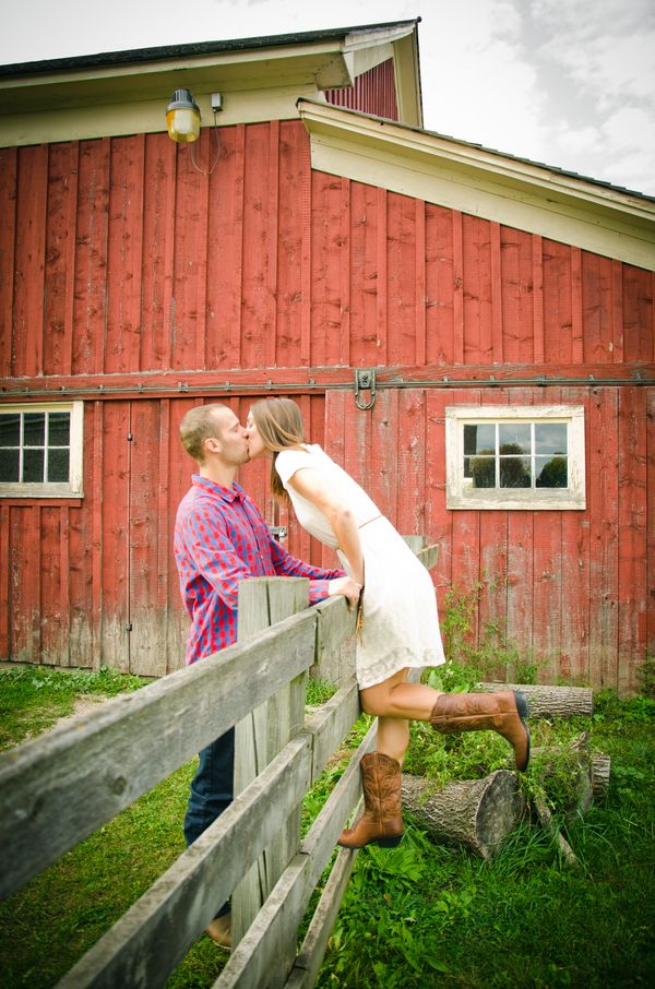 Rustic Barn Engagement Photo Cowboy boots Wisconsin Country Fence Kiss Light Source Photography