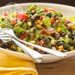 Zwarte bonen, mais, rode paprika en geroosterde pompoenzaadjes worden gemengd met een romige, zelfgemaakte dressing van avocado, limoensap en koriander voor een kleurrijke, smaakvolle salade!