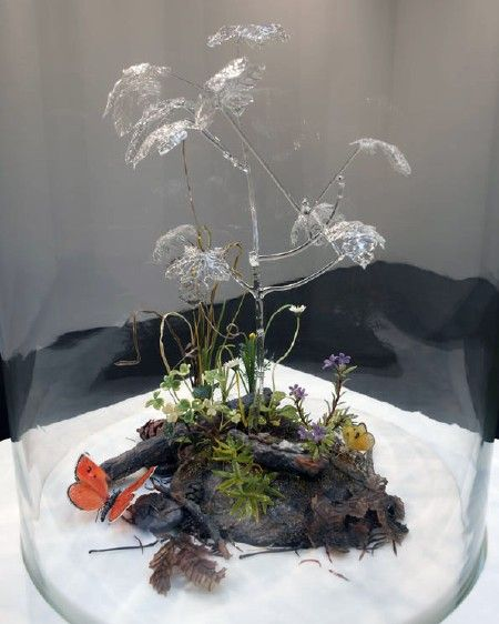 """...a tangled diorama covered by a large bell jar...  Inside, a lump of earth seemed to sustain a few examples of scraggly plant life, as well as a scattering of dead leaves and a couple of brightly coloured butterflies. Above it, a larger plant might have given the scene some shade were it not made entirely of clear glass. This strange form gives the lie to the rest of the construction: every element in the piece, from the pine needles to the ladybird that can be spied in the undergrowth…"