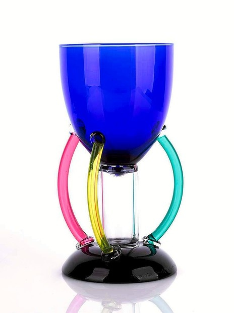 Ettore Sottsass Memphis Deneb Glass Goblet, designed 1982 the bowl of blue glass with three applied loop handles in varying colours, the stem clear, on a deep purple circular foot, signed underside Measurements height 20cm Sold for $1080 IBP