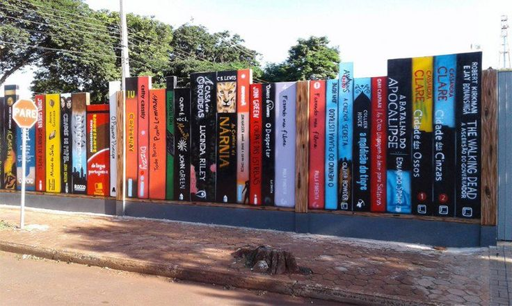 """O Colégio Evangélico Martin Luther, que fica em Marechal Cândido Rondon, no Paraná, fez uma reforma em seu muro com uma arte repleta de lombadas de livros. A """"prateleira"""" de obras é do artista Alexandre Schwingel, o Trilha, que já tem vários grafites nos muros da cidade.  Entre os títulos que integram a parede estão """"A Culpa é das Estrelas?"""", de John Green; """"As Crônicas de Nárnia"""", de C.S. Lewis, e a coletânea """"Toda Poesia"""", de Paulo Leminski."""