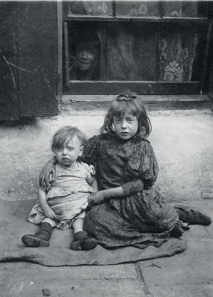 Ragamuffins: Annie, seven, and one-year-old Nellie, sit sad and hungry on sacking outside their house in Spitalfields. They were among ten children born to single mother Annie Daniels. Five of their siblings died in childhood