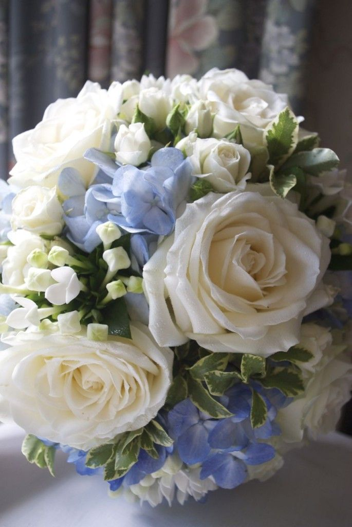 Blue and white wedding bouquet of roses, hydrangea and bouvardia
