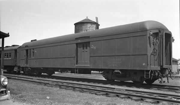 RAILWAY POST OFFICE (RPO) Car #738, is shown here at Oyster Bay , taken on May 6, 1951, only viewed from the opposite angle.  The car is sporting terrific kerosene marker lamps and the old water tower is visible behind the car.  It is still in the Pennsylvania Railroad Tuscan Red color scheme with gold Dulux lettering. (George E. Votava photo)