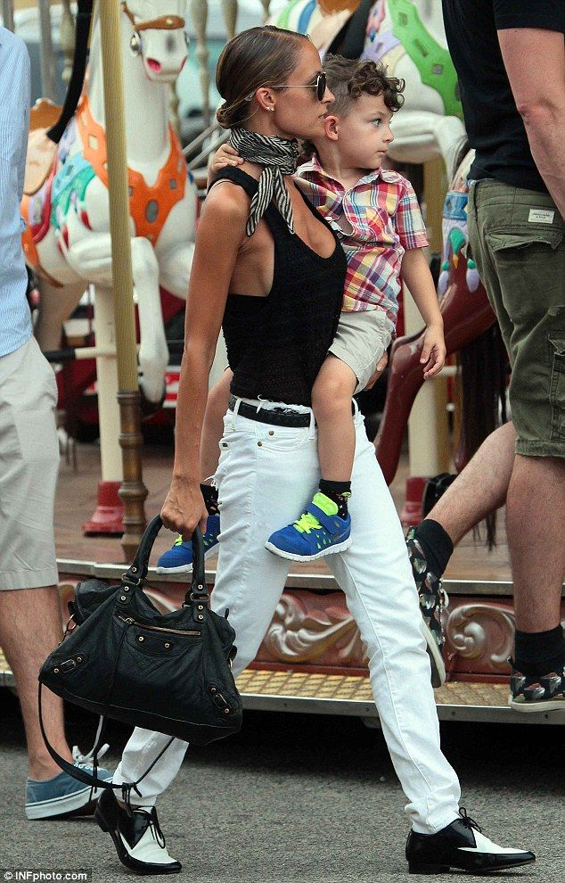 My turn mom! The stylish star carries her son who looks eager and ready to ride