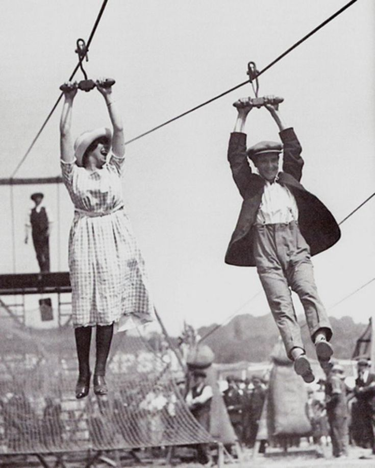 A couple enjoy a old style zipline in 1923. Not many people could hold on with just their hands these days