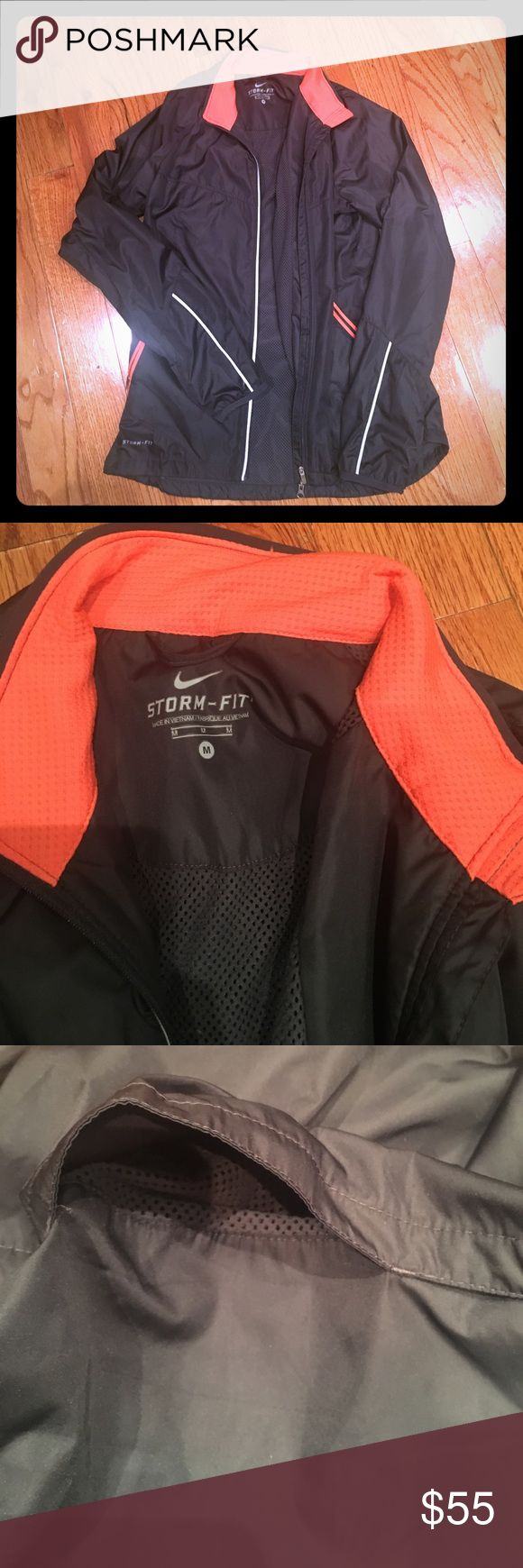 Medium women's Nike storm fit zip up jacket This is an extremely comfortable Nike storm fit zip up jacket in gray with orange lining. Two side pockets and one back pocket for keys and credit cards. Until later flap on back. Collared. Comfortable inner lining and wind and water protective outer lining. Nike Jackets & Coats
