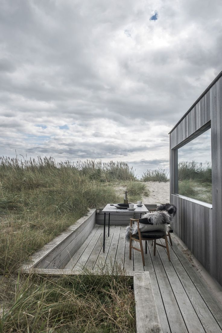 Summer Cottage G18, a pitched roof summer home in Denmark uses cedar cladding and roofing material giving the impression of a silver wooden block or piece of driftwood to blend in with the surrounding landscape of dunes and beach. By Ardess