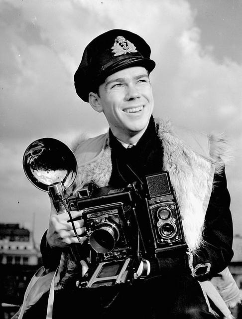 Lieutenant John D. Mahoney of the Royal Canadian Navy Volunteer Reserve, holding an Anniversary Speed Graphic camera, 1944.