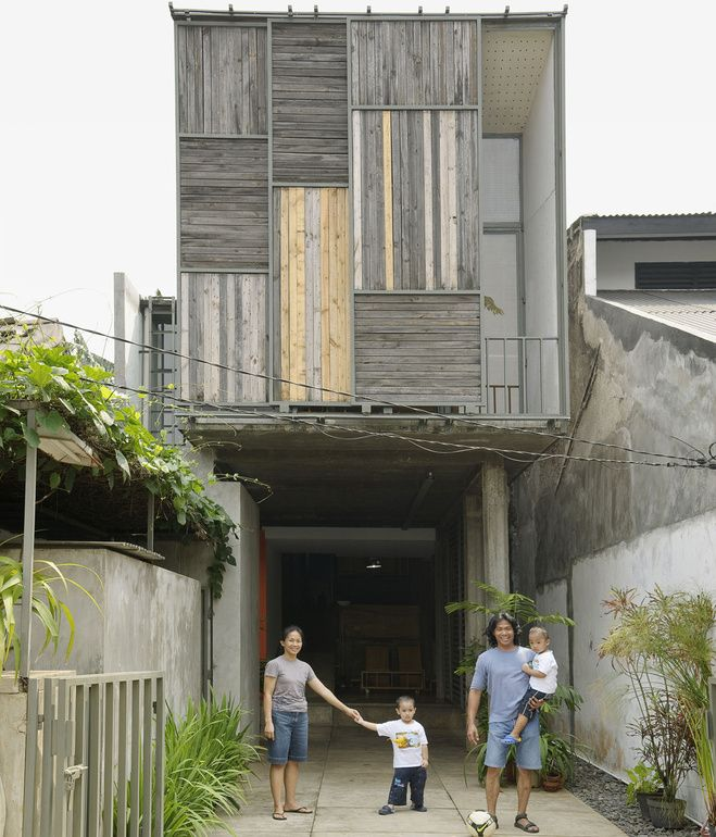 Bekasi home. The family poses in the driveway out front of the house. The sliding panels on the facade allow a peek into the balcony just inside.  Pho...