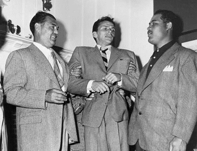 Frank Sinatra held up by heavyweight boxing legends Jack Dempsey and Joe Louis circa 1947.